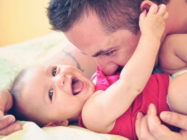 Father cuddling with smiling baby