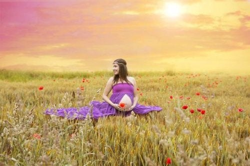 Pregnant woman in a sunny field with flowers