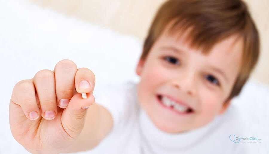 Boy smiling and showing a tooth in his hand