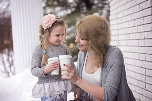 Mom and daughter holding to-go cups