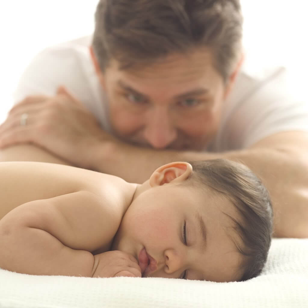 Father looking at sleeping baby