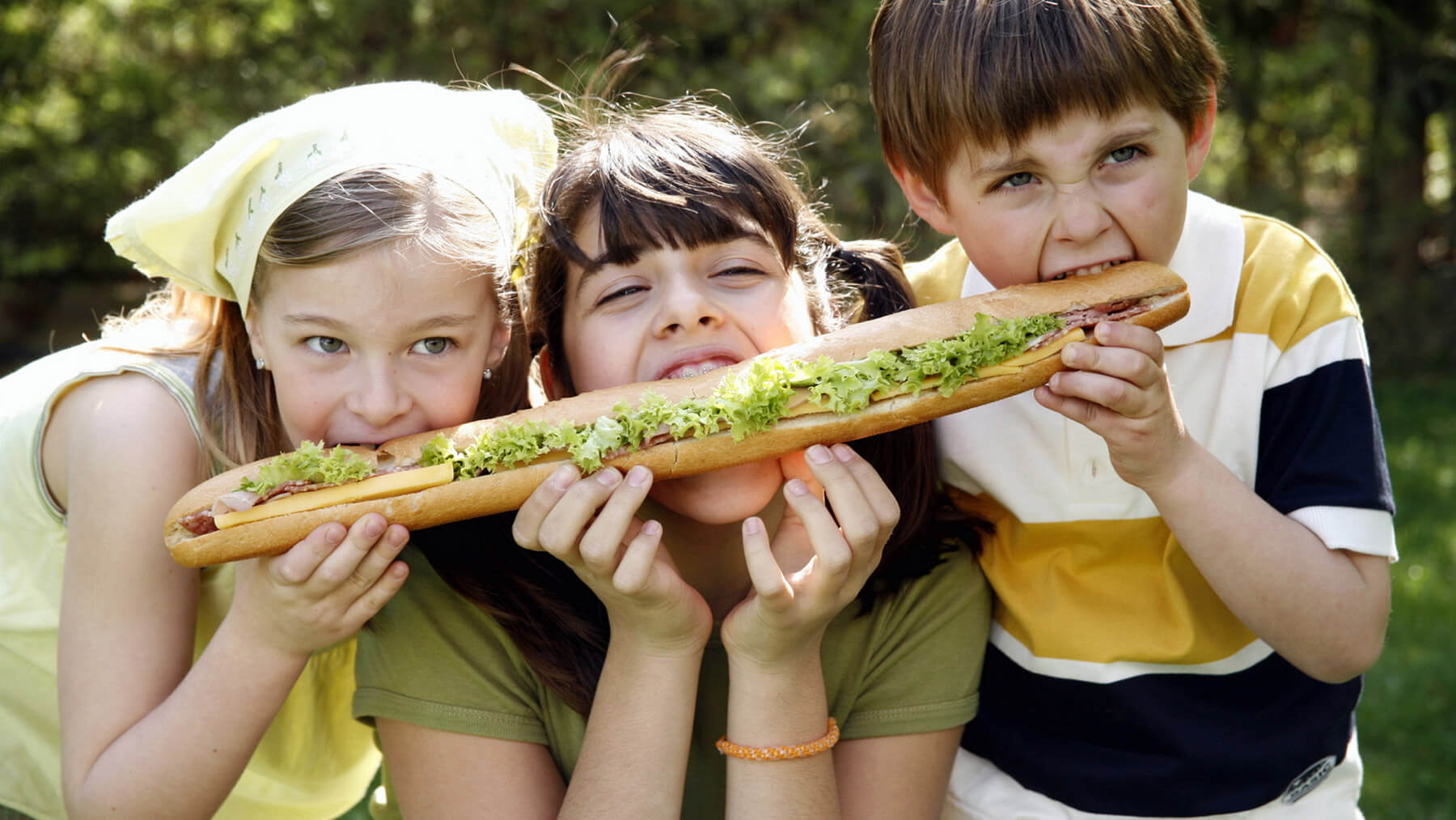 Three children sharing a sandwich