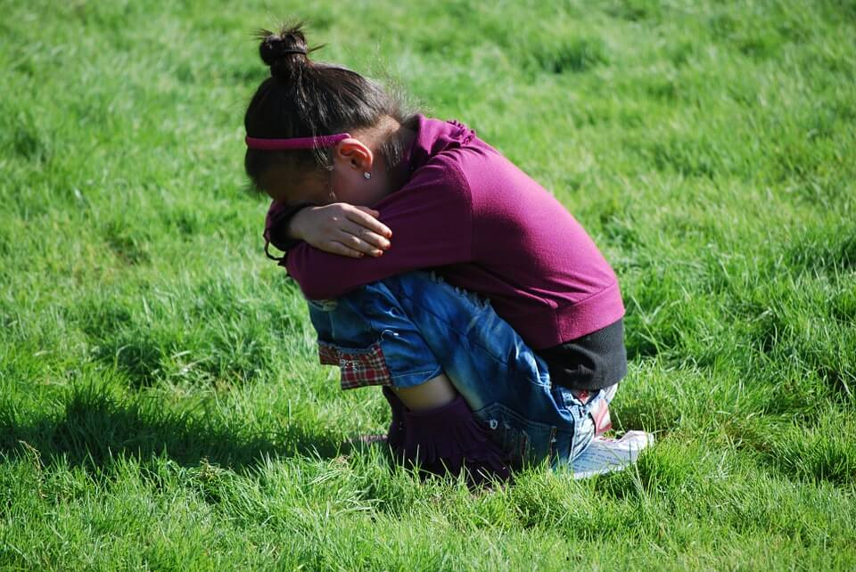 Girl crying alone in the grass