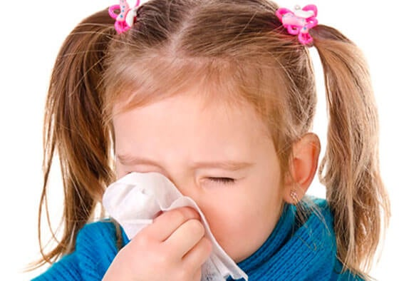 girl blowing her nose with a cold