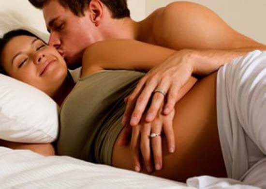Pregnant woman and husband lying in bed smiling