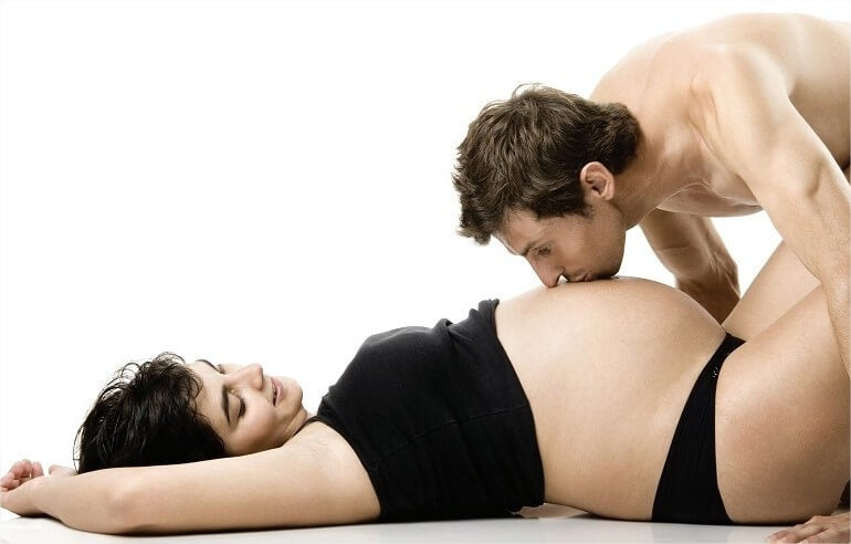 Man kissing belly of pregnant woman