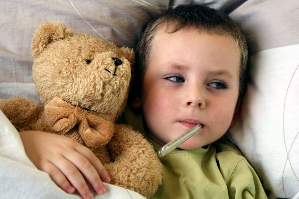 boy with a thermometer and teddy bear