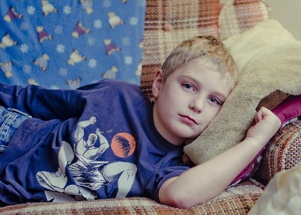 Boy lying on couch with appendicitis