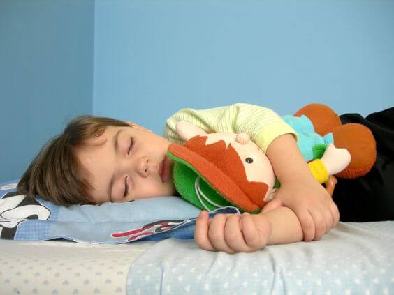 boy sleeping with stuffed animal