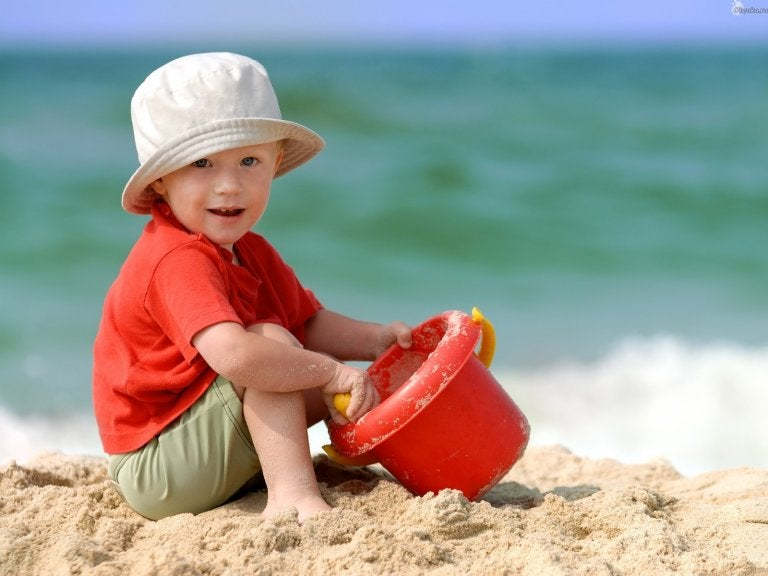 Boy playing in the sand with white hat