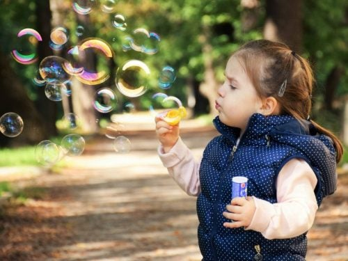 girl blowing bubbles in the park