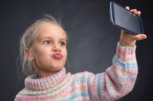 child holding cell phone taking selfie
