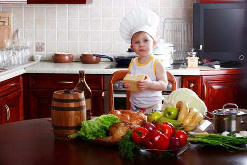 toddler in kitchen wearing a chef hat