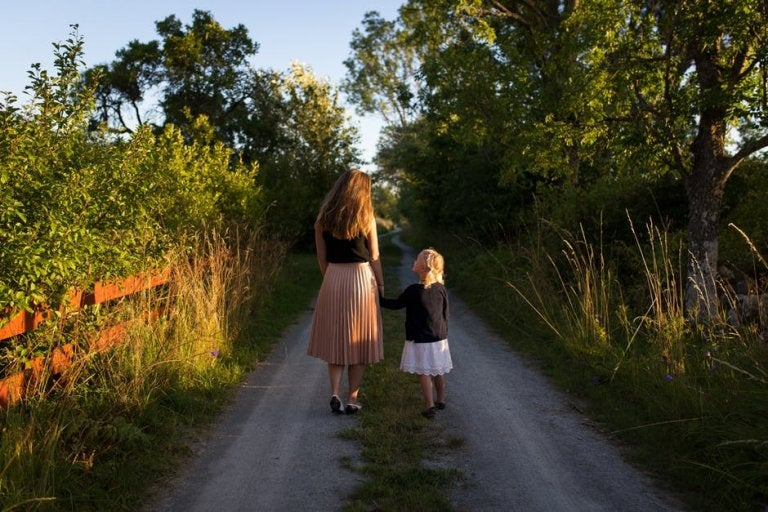 Mom holding daughter's hand in nature
