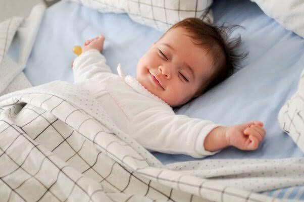 baby smiling while sleeping in large bed
