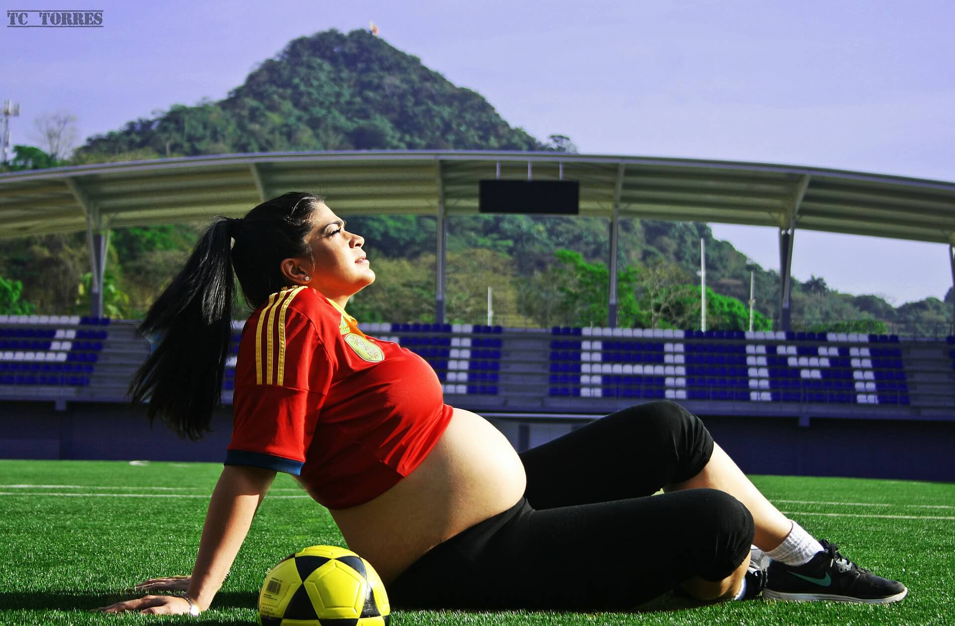 pregnant woman sitting on soccer field