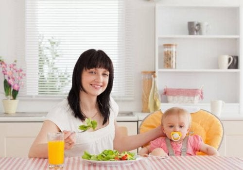 mom eating a salad next to her baby