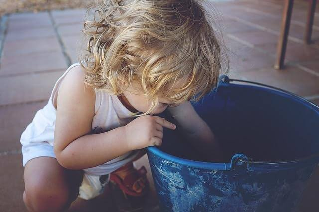 child reaching into a blue bucket