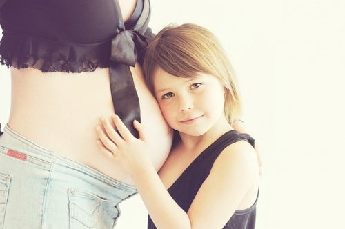 girl resting her head on her mom's pregnant belly