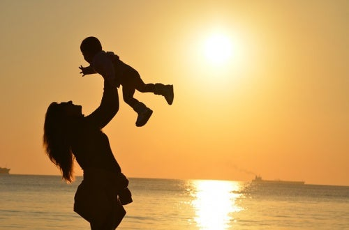 silhouette of mom holding baby up in the air
