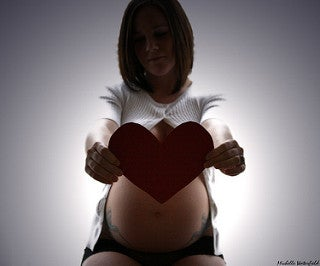 pregnant woman holding a heart