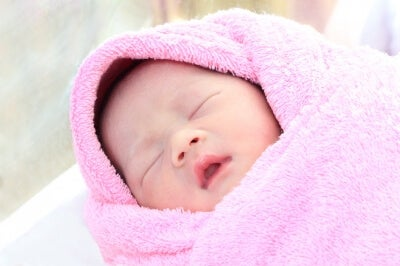 baby bundled up in a pink blanket