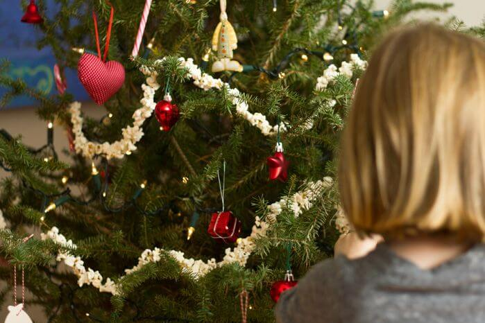 mom thinking about toys beside christmas tree