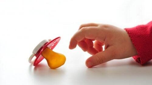 babyhånd der rækker ud efter sut