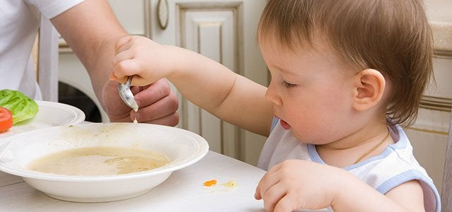 lille barn der spiser suppe med en ske selv