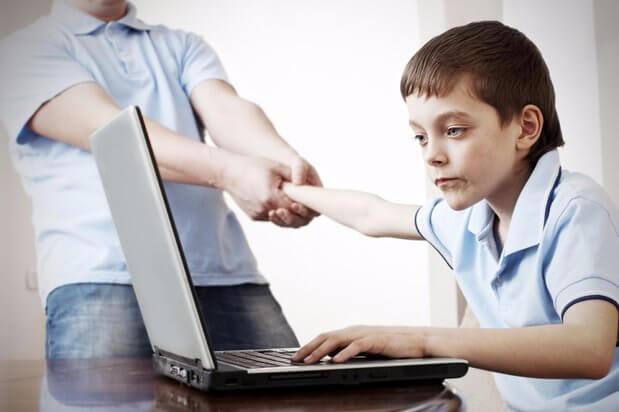 forælder der prøver at hive dreng væk fra computer