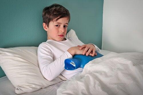 lille dreng med varmepude på maven