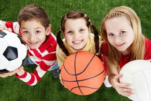 Tre glada barn tittar in i kameran och håller i bollar
