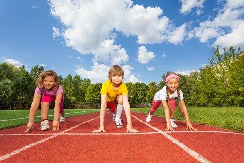 tre børn klar til løb på løbebane