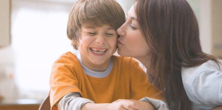 mor der kysser smilende dreng på kinden