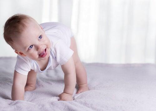 baby der forsøger at rejse sig i en seng