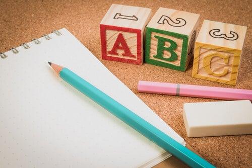 blyant, papir og blokke med bogstaver