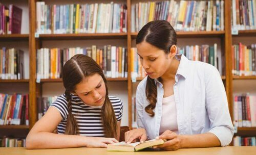Lärare och elev studerar bok tillsammans