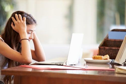 Flicka tittar med frustration på sitt skolarbete