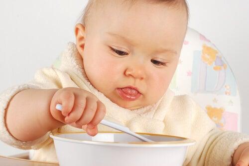 lille baby der spiser med en ske