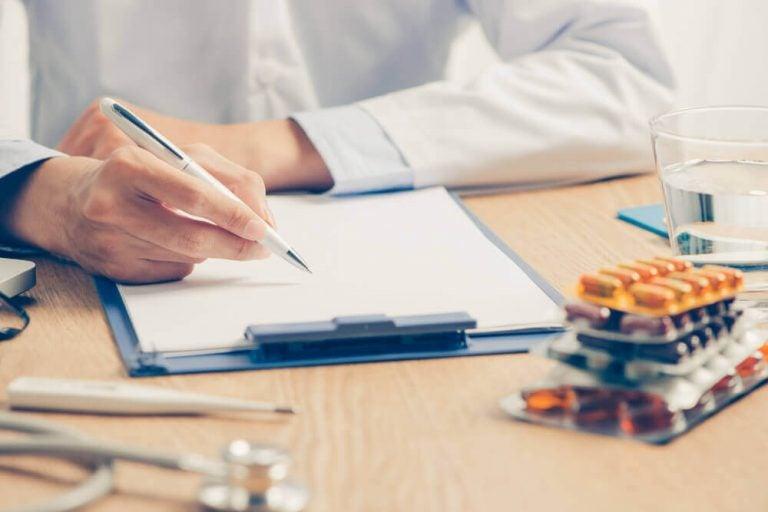 skrivebord hos læge der skriver