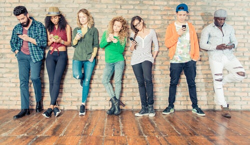 teenagere på række op ad væg med telefoner i hånden