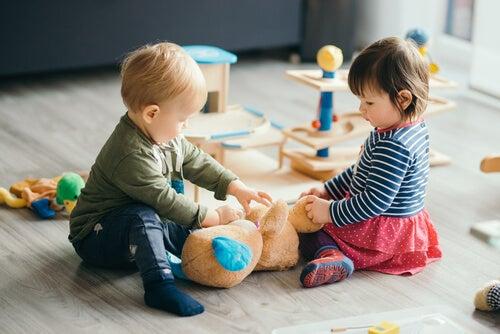 to små børn der leger med en bamse