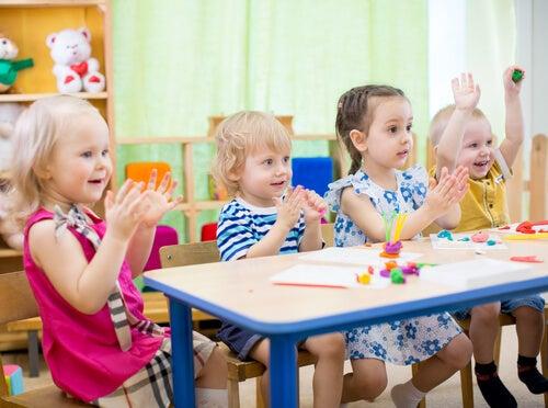 børn der sidder ved bord og klapper
