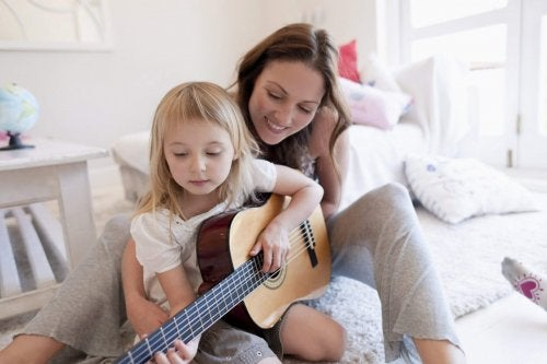 mor og datter der øver på en guitar