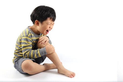 dreng i smerter der tager sig til knæet