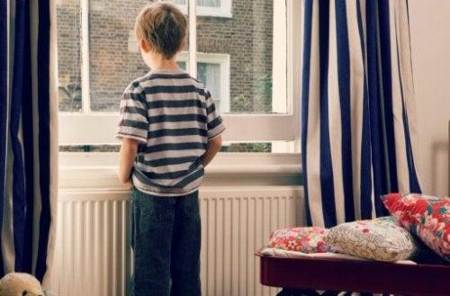 lille dreng der kigger ud af et vindue