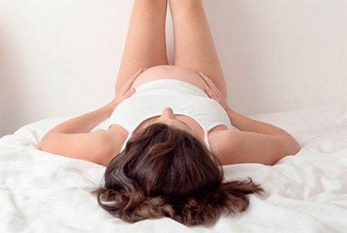 gravid kvinde med ben op ad væg i seng