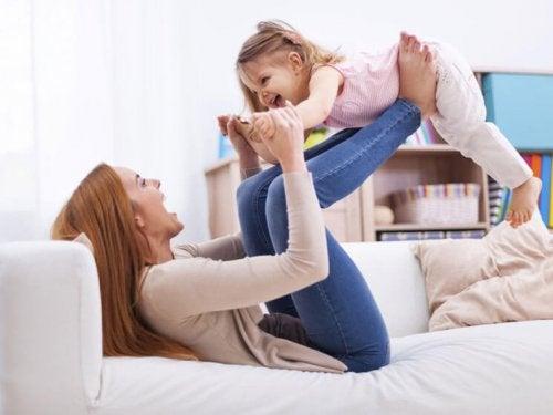 kvinde der løfter pige med sine ben i sofa