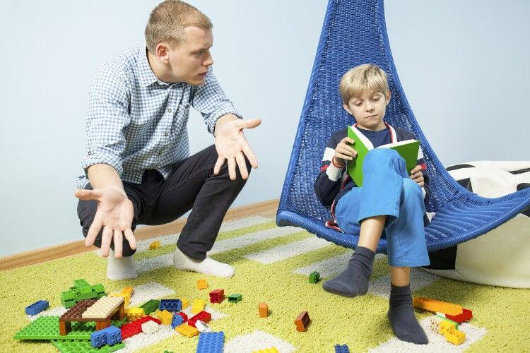 frustreret far der vil have læsende dreng til at rydde op