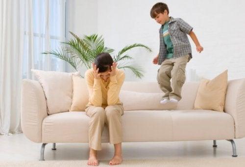 frustreret mor med dreng der hopper i sofa